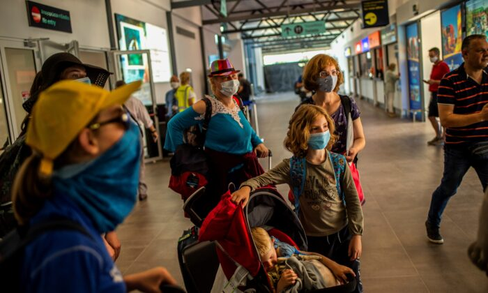 Passengers of a flight from Budapest wearing protective face masks arrive at the Corfu Airport Ioannis Kapodistrias on Corfu Island on July 1, 2020. (Angelos Tzortzinis /AFP via Getty Images)
