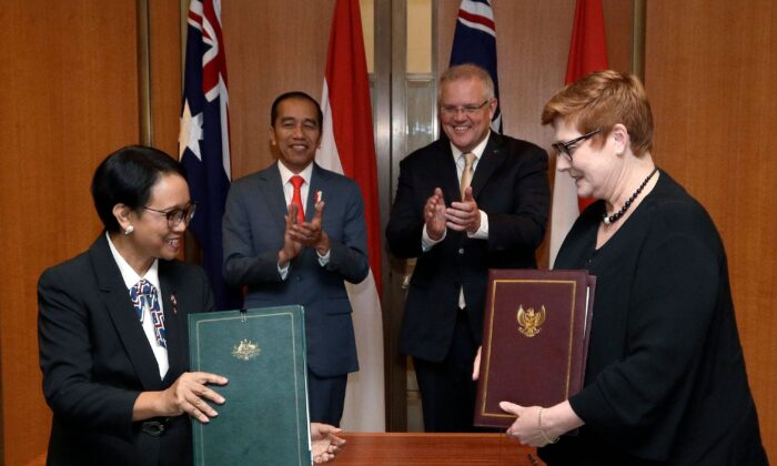 Indonesias President Joko Widodo (centre L) and Australias Prime Minister Scott Morrison (centre R) watch as Indonesia's Foreign Minister Retno Marsudi (L) and Australia's Foreign Minister Marise Payne (R) sign agreements at Parliament House in Canberra, Australia, on Feb. 10, 2020. (RICK RYCROFT/POOL/AFP via Getty Images)