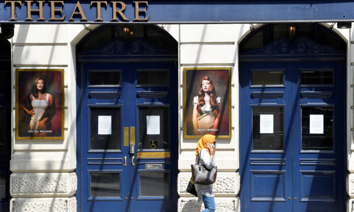 A woman wearing a protective face mask walks past a closed theatre following the spread of the coronavirus disease (COVID-19) in London, Britain, on June 23, 2020. (Toby Melville/Reuters)