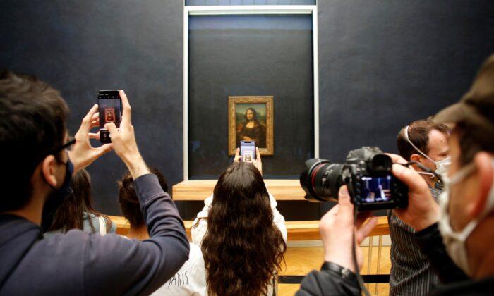 Visitors take photos of the Leonardo da Vinci's painting Mona Lisa, in Paris, France, on July 6, 2020. (Thibault Camus/AP Photo)