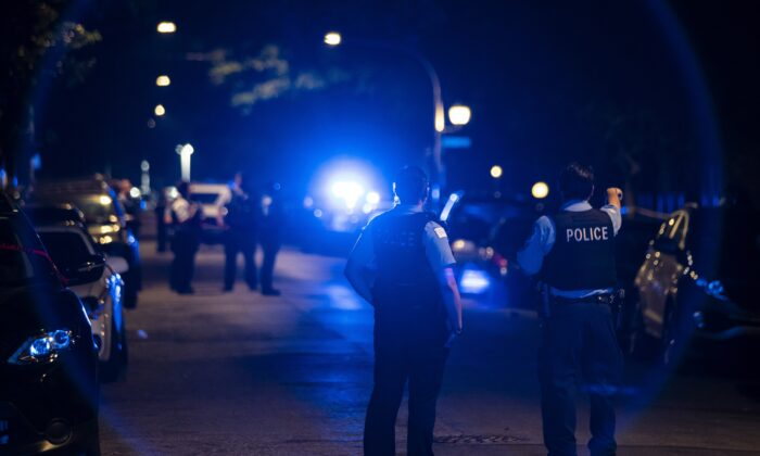 Chicago police officers investigate the scene of a shooting in Chicago on July 5, 2020. (Ashlee Rezin Garcia/Chicago Sun-Times via AP)