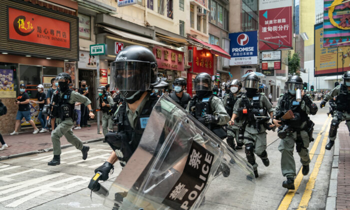 Riot police run on a street toward pedestrians during a crowd control operation at a demonstration in Hong Kong, on July 1, 2020. (Anthony Kwan/Getty Images)