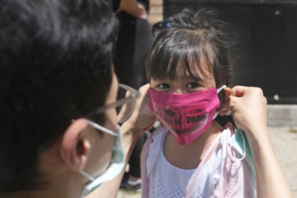 Olivia Chan's father helps her with a new mask