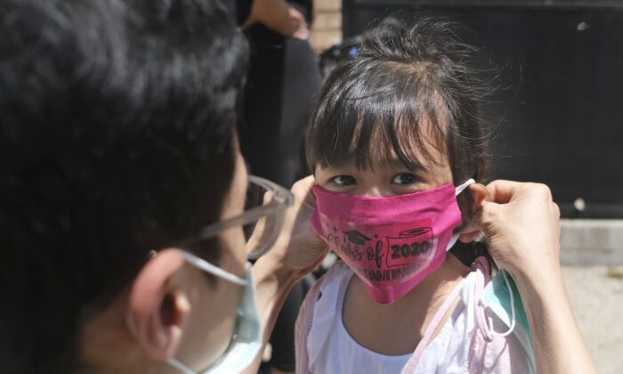 Olivia Chan's father helps her with a new mask she received during a graduation ceremony for her Pre-K class in front of Bradford School in Jersey City, N.J. on June 10, 2020. (Seth Wenig/AP)