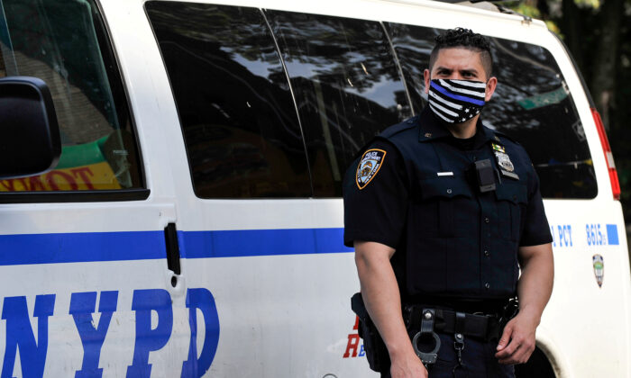 An NYPD police officer wears a Blue Line mask indicating support for law enforcement in Brooklyn, N.Y., on June 25, 2020. (Lloyd Mitchell/Reuters)