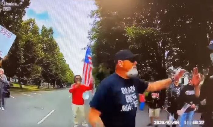 """An Oregon State Police officer, right, makes an """"ok"""" hand signal while speaking to a man at a protest in Salem, Ore., on July 4, 2020. (Oregon State Police)"""