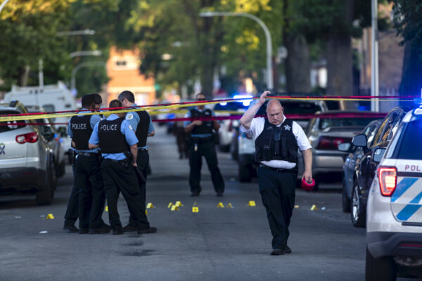 Chicago police officers investigate the scene of a deadly shooting