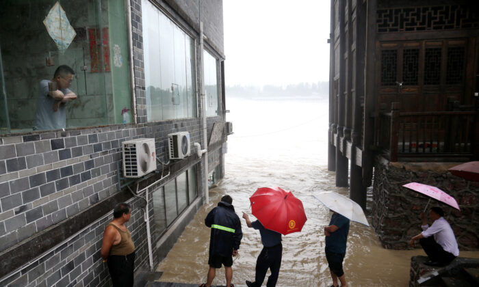 People observe the rising water level of a river at the flood-hit Zhuoshui ancient town, following heavy rainfall in Chongqing's Qianjiang district, China, on June 28, 2020. (China Daily via Reuters)
