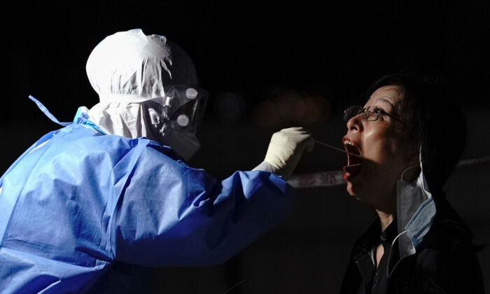A medical worker takes a swab sample at a test station in Beijing on July 6, 2020. (Lintao Zhang/Getty Images)