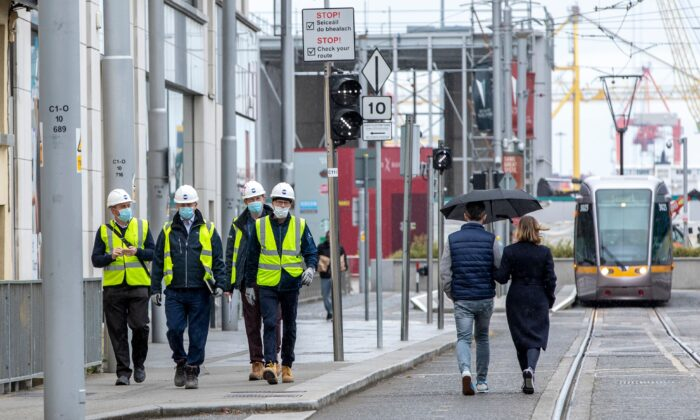 Construction workers wearing protective face masks make their way to a site along the Quays, in Dublin City centre in Ireland, on May 18, 2020. (Paul Faith/AFP via Getty Images)