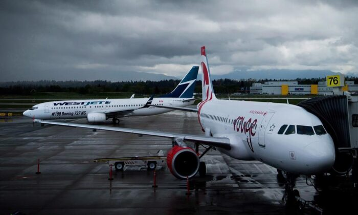 A Westjet Boeing 737-800 (L) taxis past an Air Canada Rouge Airbus A319 at Vancouver International Airport in Richmond, B.C., on April 28, 2014. (The Canadian Press/Darryl Dyck)