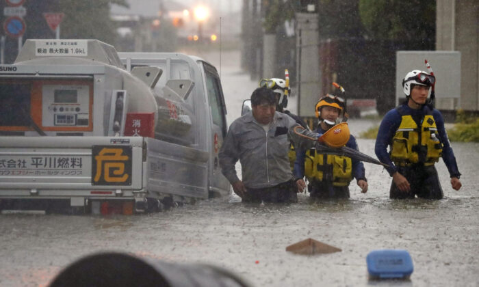 A man is rescued by police officers after his car became stuck on a flooded road caused by torrential rain in Omuta, Fukuoka prefecture, southern Japan, on July 7, 2020. (Kyodo/Reuters)