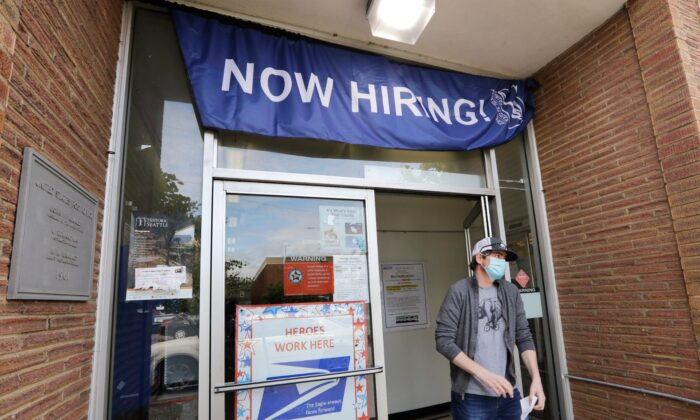 A customer walks out of a U.S. Post Office branch and under a banner advertising a job opening, in Seattle, Wash., on June 4, 2020. (Elaine Thompson/File/AP Photo/)