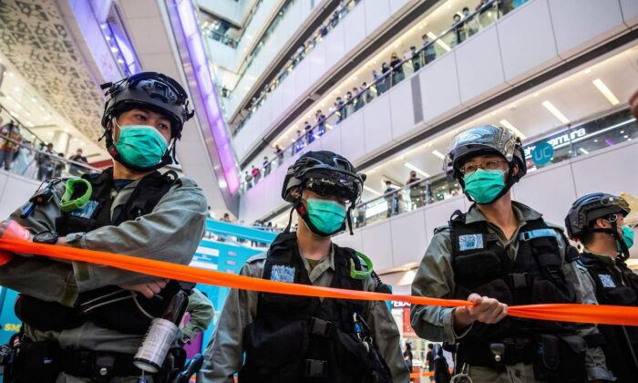 Riot police stand guard during a clearance operation during a demonstration in a mall in Hong Kong on July 6, 2020. (Isaac Lawrence/AFP via Getty Images)