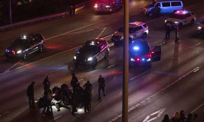 Emergency workers tend to an injured person on the ground after a driver hit two of a group that was blocking the Interstate 5 freeway in Seattle on July 4, 2020. (James Anderson via AP)
