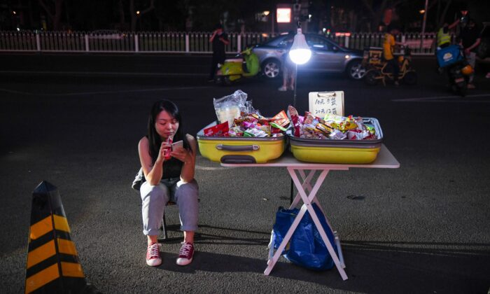 A street vendor waits for customers on the roadside outside a shopping mall in Beijing on June 10, 2020. (GREG BAKER/AFP via Getty Images)