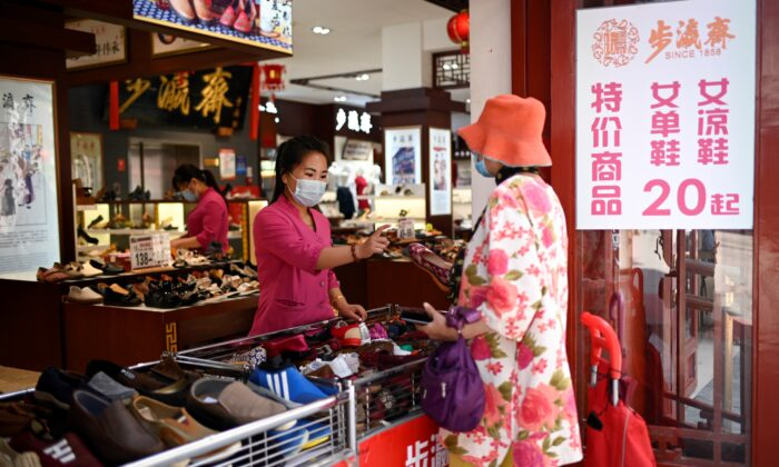 A shopper chooses shoes that cost 20 yuan ($2.86) per pair in Beijing on June 30, 2020. (Wang Zhao/AFP via Getty Images)