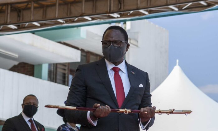 Malawi President elect Lazarus Chakwera shows the sword of office to the people after he received it from the Commander of the Malawi Defence Force, Gen. Peter Namathanga, during his inauguration at the Kamuzu Baracks, the Malawi Defence Fore Headquarters, in Lilongwe, on July 6, 2020. (Amos Gumulira/AFP via Getty Images)