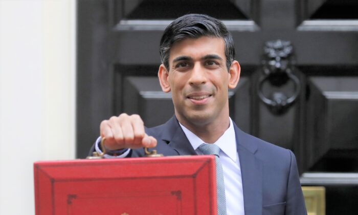 Britain's Chancellor of the Exchequer Rishi Sunak stands outside No 11 Downing Street and holds up the traditional red box that contains the budget speech for the media, he will then leave to make budget speech to House of Commons, in London on March 11, 2020. Sunak is set to announce Wednesday a 2 billion pound ($2.5 billion) program to create jobs for young people as the government tries to revive an economy battered by the COVID-19 pandemic. (AP Photo/Kirsty Wigglesworth)