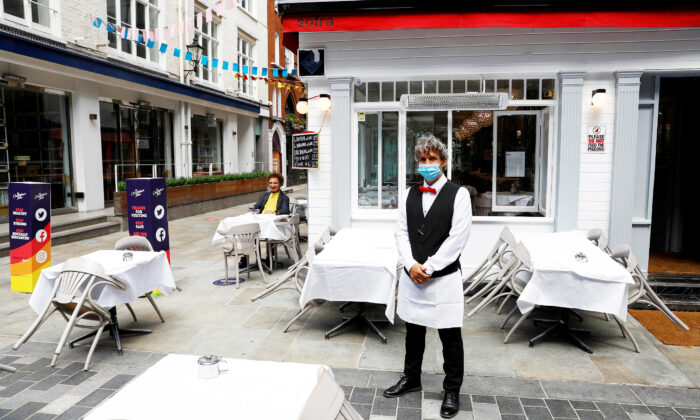 A waiter poses for photographs as he waits for customers outside a restaurant, after it reopened following the coronavirus disease (COVID-19) outbreak, in London, Britain, on July 5, 2020. (Peter Nicholls/Reuters)