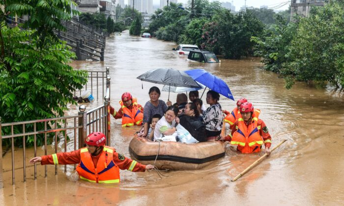 Rescuers evacuate flood-affected residents following heavy rain in Jiujiang in China's central Jiangxi province on July 8, 2020. (STR/AFP via Getty Images)
