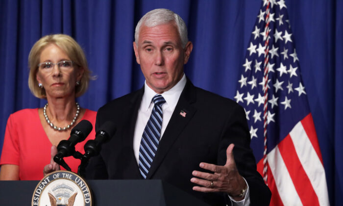 Vice President Mike Pence speaks as Secretary of Education Betsy DeVos listens during a White House Coronavirus Task Force press briefing at the U.S. Department of Education in Washington on July 8, 2020. (Alex Wong/Getty Images)