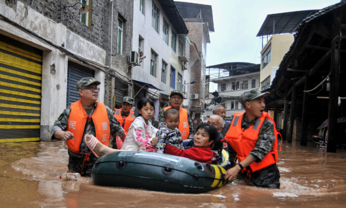 This photo taken on June 28, 2020 shows rescuers evacuating residents in a flooded area after heavy rain in China's southwestern Chongqing. (STR/AFP via Getty Images)