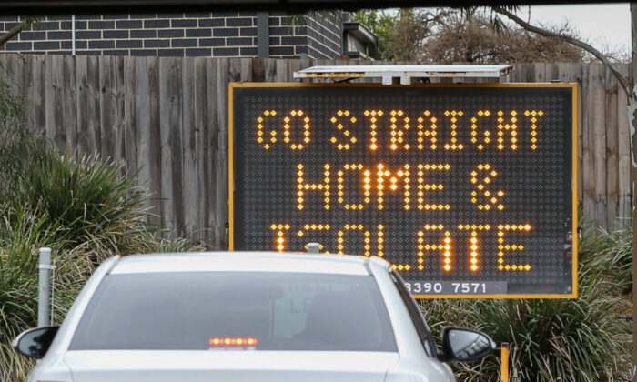 A sign reading 'Go straight home and Isolate' is seen at the exit of a drive through COVID-19 testing site at Highpoint shopping centre on July 4, 2020 in Melbourne, Australia. (Asanka Ratnayake/Getty Images)