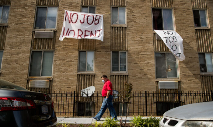 "Signs that read ""No Job No Rent"" hang from the windows of an apartment building in Washington on May 20, 2020. (Andrew Harnik/AP Photo)"