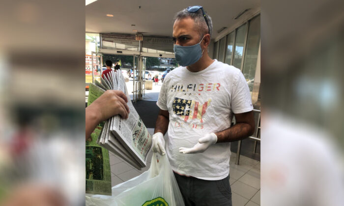 A man is confronted by an Epoch Times staff member (not seen in frame) after he was spotted taking more than 10 copies of The Epoch Times newspaper from a location in Toronto on July 4, 2020. (The Epoch Times)