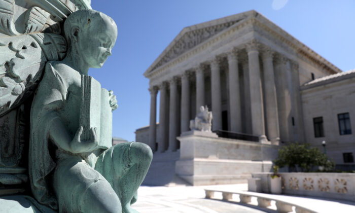 A cherub figure with a book, symbolizing learning, is seen in a general view of the U.S. Supreme Court building in Washington, on July 2, 2020. (Jonathan Ernst/Reuters)