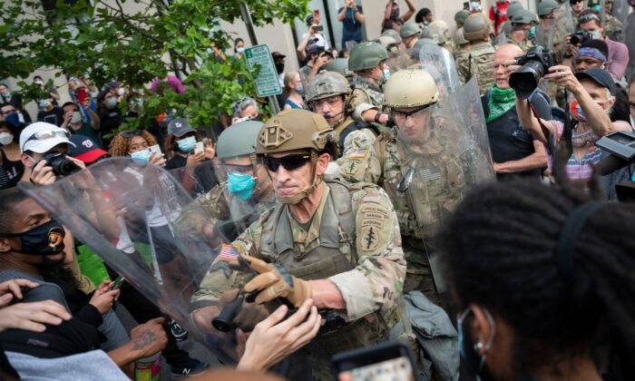Protesters scuffle with members of the US Army as they demonstrate the death of George Floyd near the White House in Washington on June 3, 2020. (Jim Watson//AFP via Getty Images)