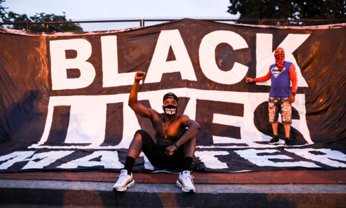 Protesters pose in front of a Black Lives Matter sign near the White House following the May 25 death of George Floyd in police custody, in Washington on June 6, 2020. (Charlotte Cuthbertson/The Epoch Times)