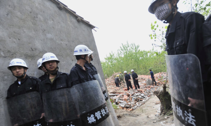 Chinese security agents carry sticks as they stand guard while workers demolish houses in Wuhan, central China's Hubei Province on May 7, 2010. (AFP/AFP via Getty Images)