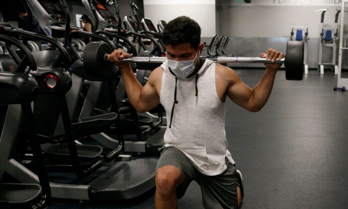 People wear masks while exercising at a gym in Los Angeles, on July 9, 2020. (Jae C. Hong/AP)