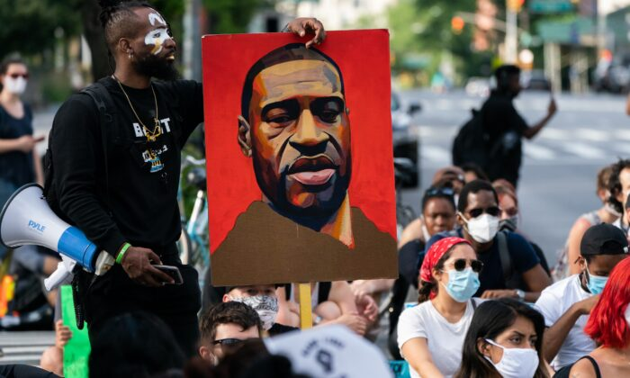 A man holds a picture of George Floyd during a Black Lives Matter protest in New York City on June 18, 2020. (Jeenah Moon/Getty Images)
