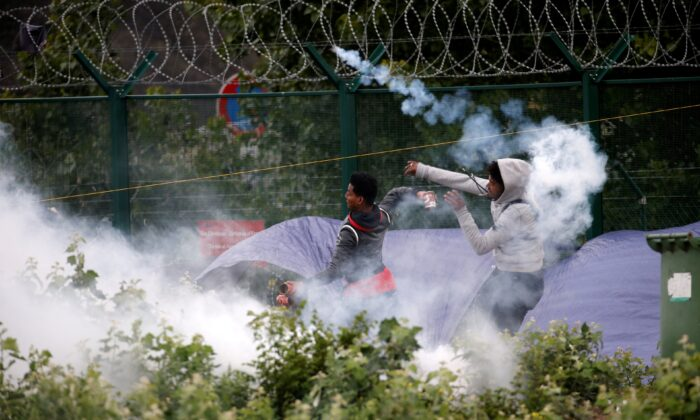 Migrants throw objects at French police officers in a cloud of tear gas as police dismantle a makeshift shelter camp in Calais, France, on July 10, 2020. (Pascal Rossignol/Reuters)