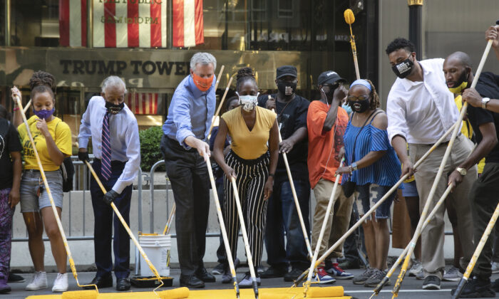 Mayor Bill de Blasio, third from left, participates in painting Black Lives Matter on Fifth Avenue in front of Trump Tower, in New York on July 9, 2020,. The mayor's wife, Chirlane McCray, is fourth from left and Rev. Al Sharpton is second from left. (AP Photo/Mark Lennihan)