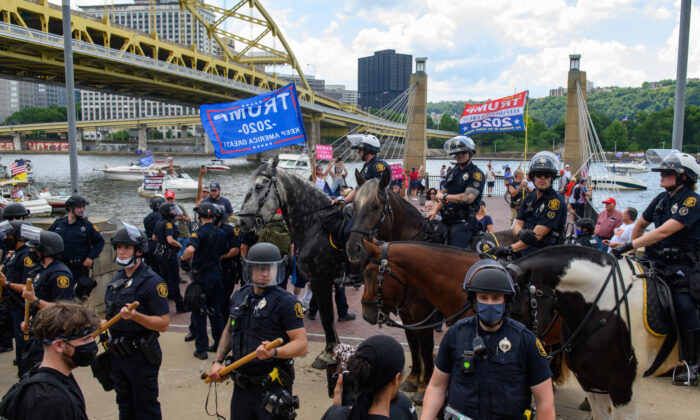 Pittsburgh Police in riot gear intervene between a group of Black Lives Matter protestors confronting a group of Trump supporters while they wait along the Allegheny River North Shore for a flotilla of boats taking part in a boat parade for the re-election of President Donald Trump to pass by on July 4, 2020 in Pittsburgh, Penn. (Jeff Swensen/Getty Images)