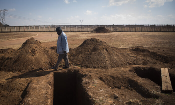 A worker walks past a freshly dug grave at the Honingnestkrans cemetery, near Pretoria, South Africa, on July 9, 2020. (Shiraaz Mohamed/AP)