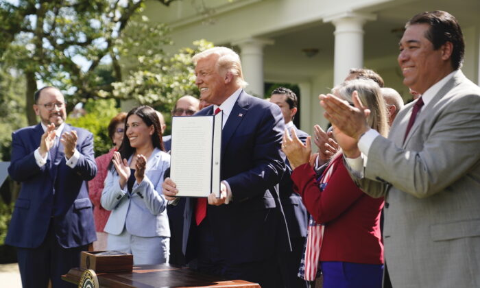 "President Donald Trump holds an executive order on the ""White House Hispanic Prosperity Initiative,"" after signing it in the Rose Garden of the White House, in Washington, on July 9, 2020. (Evan Vucci/AP Photo)"