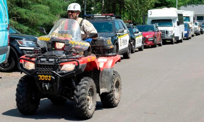 A police officer drives his quad on a street, on July 10, 2020 in Saint-Apollinaire, Que. (Jacques Boissinot/The Canadian Press)