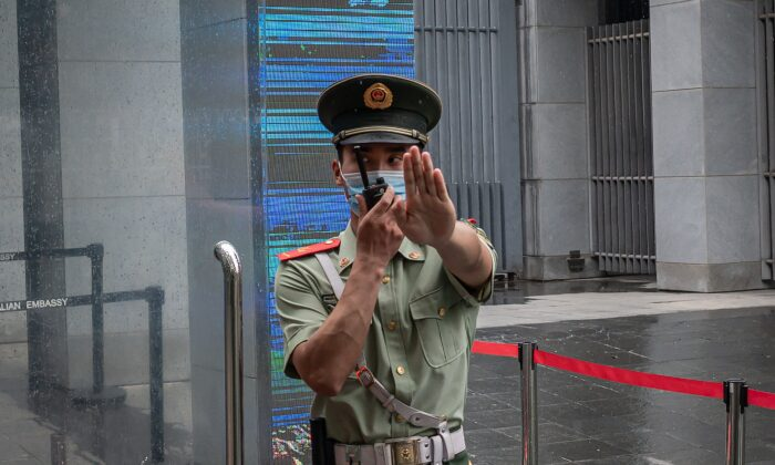 A Chinese paramilitary police officer gestures and speaks over his two-way radio whlie standing at the entrance gate of the Australian embassy in Beijing on July 9, 2020. (Nicolas Asfouri/AFP via Getty Images)