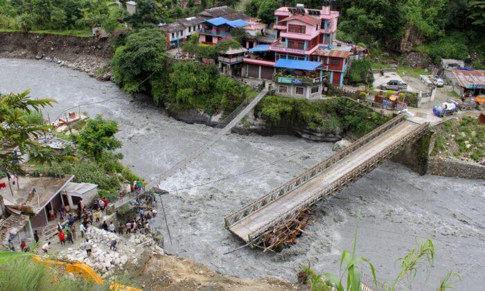 People gather near the bridge that is damaged due to the flood at Raghu Ganga River in Myagdi, Nepal July 11, 2020. (Santosh Gautam/Reuters)