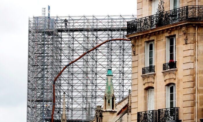A worker stands on a scaffolding at Notre Dame cathedral, in Paris, France, on July 10, 2020. (Thibault Camus/AP Photo)