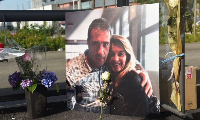 A picture of Veronique Monguillot and Philippe Monguillot, a bus driver declared brain dead after being attacked for refusing to let aboard a group of people who were not wearing face masks, is displayed during a white march in Bayonne, southwestern France, on July 8, 2020. (Iroz Gaizka/AFP via Getty Images)