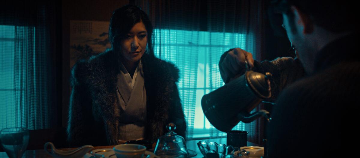 "woman in fur coat sitting at table in ""In Full Bloom"""