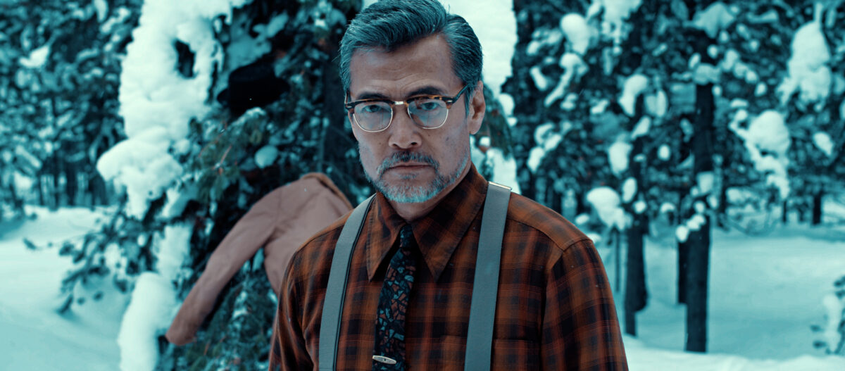 """Japanese man in plaid shirt and supspenders in snowy woods in """"In Full Bloom"""""""