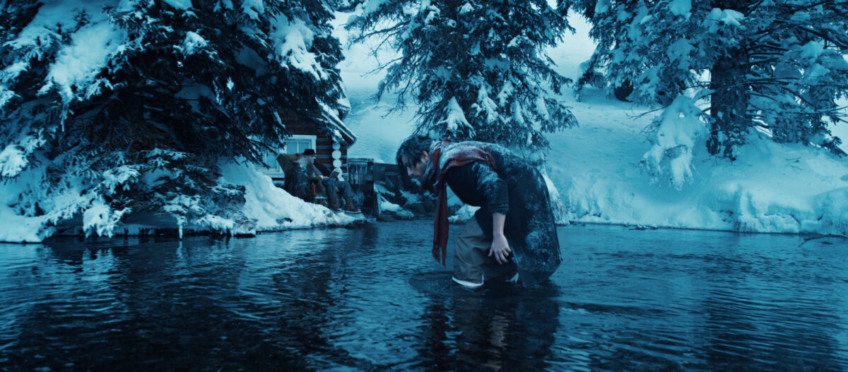 "man standing in winter pond in ""In Full Bloom"""