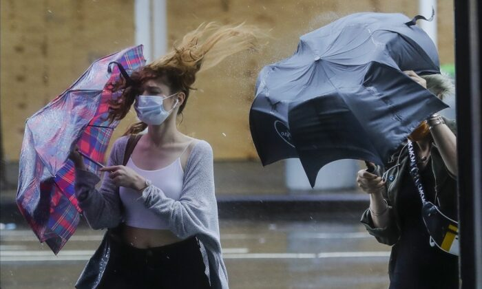 Pedestrians struggle to control their umbrellas due to inclement weather brought about by Tropical Storm-turned-Depression Fay, in New York, on July 10, 2020. (AP Photo/Frank Franklin II)